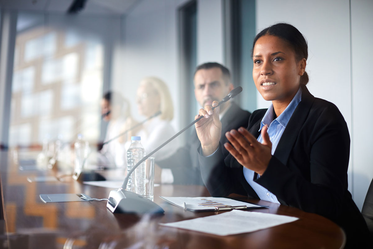 Professional woman speaking with a microphone at a global policy meeting