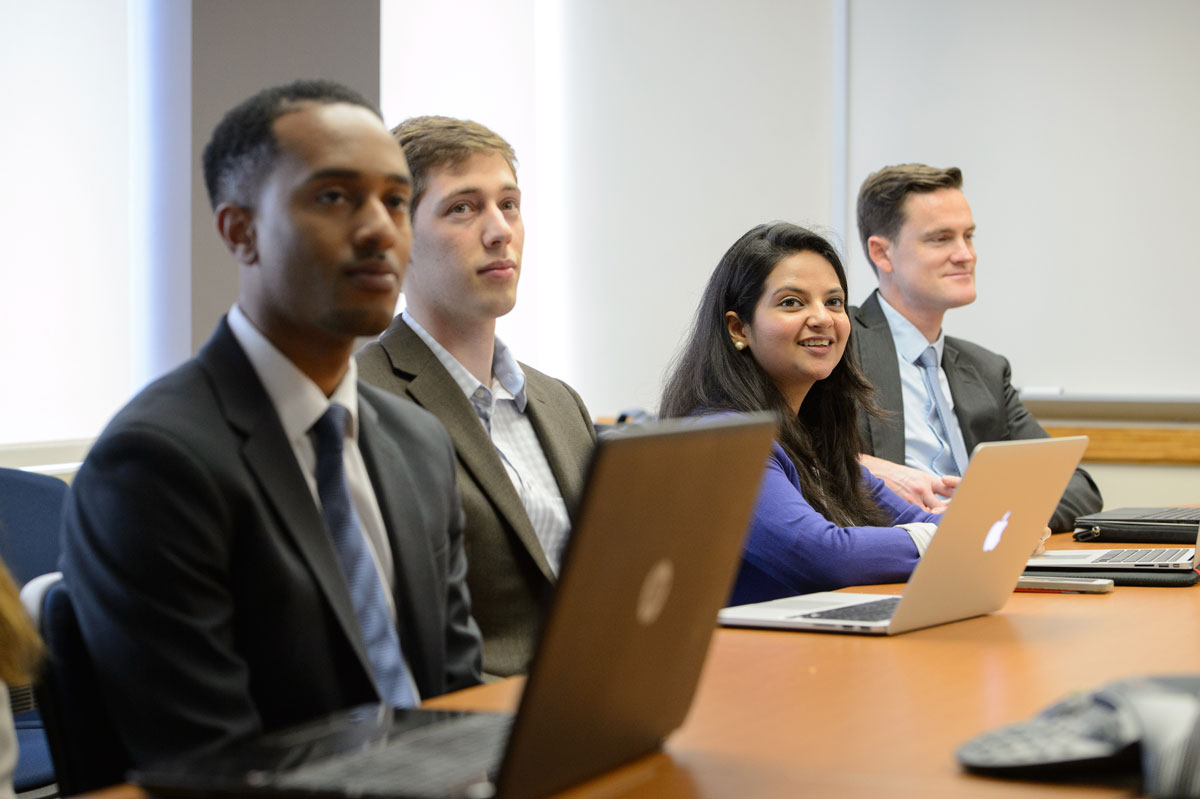 Group of SAIS students at a meeting with laptops